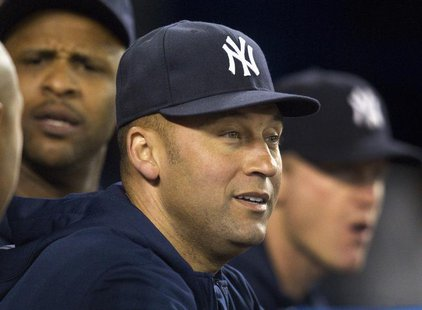 New York Yankees Derek Jeter watches play from the dugout during the seventh inning of their American League MLB baseball game against the T
