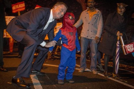 Democratic New York City mayoral candidate Bill de Blasio poses with a child dressed as Spiderman during the Park Slope Halloween Parade in