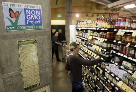 Employees stock shelves near a sign supporting non genetically modified organisms (GMO) at the Central Co-op in Seattle, Washington October