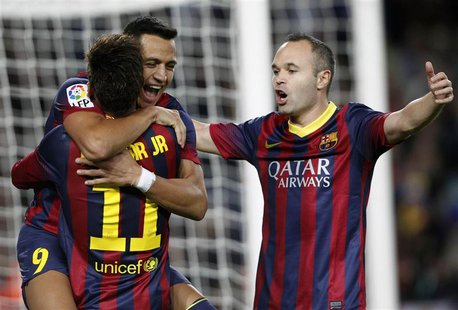 Barcelona's Alexis Sanchez (L, facing camera) celebrates a goal against Espanyol with teammates Neymar and Andres Iniesta (R) during their S