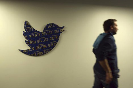 An employee walks past a Twitter logo made from Californian license plates at the company's headquarters in San Francisco, California Octobe