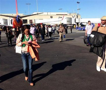 Airline passengers are evacuated to the tarmac in this picture courtesy of Natalie Morin at Los Angeles International Airport November 1, 2013. Credit: Reuters/Natalie Morin/Handout via Reuters