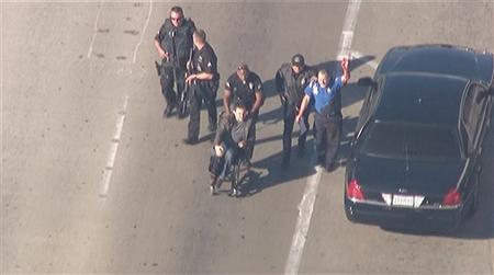 Police escort a man in a wheelchair toward medical help during an incident in which shots were fired at Los Angeles International Airport in Los Angeles in this still image taken from video provided by KNBC November 1, 2013. REUTERS/KNBC/Handout via Reuters