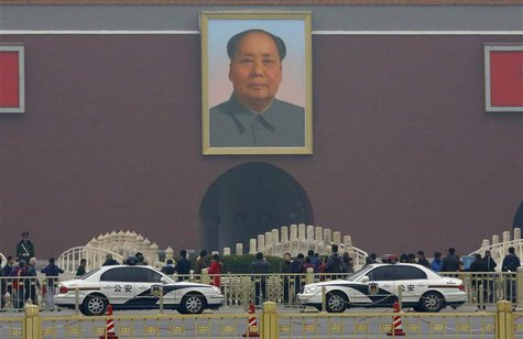 Police cars are parked in front of a giant portrait of late Chinese Chairman Mao Zedong at the main entrance of the Forbidden City in Beijin