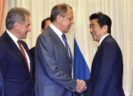 Russia's Foreign Minister Sergey Lavrov (2nd L) and Defence Minister Sergei Shoigu (L) shakes hands with Japan's Prime Minister Shinzo Abe a