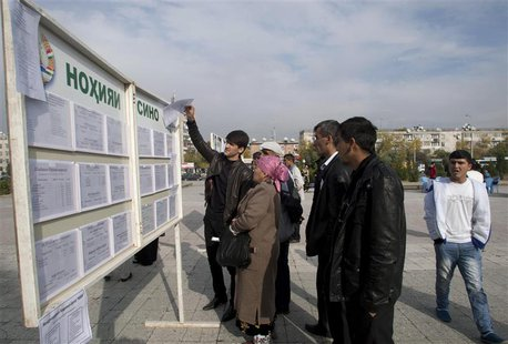 People stand in front of an information board with job vacancies in Dushanbe November 1, 2013. Tajikistan's President Imomali Rakhmon is exp