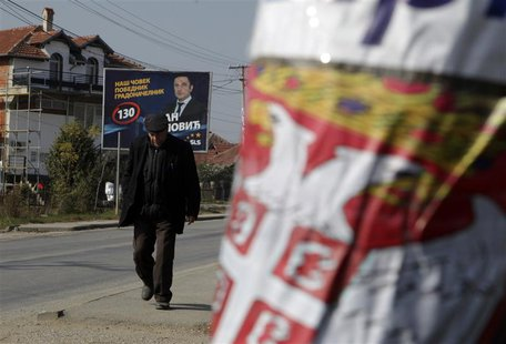 A Kosovar Serb walks past election campaign posters of Samostalna Liberalna Stranka (Independent Liberal Party) and Gradanska inicijativa Sr