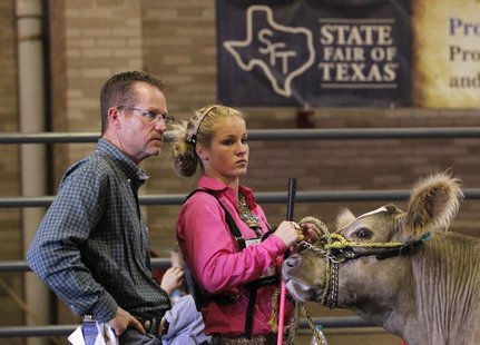 Stanley Kelley (L) and his daughter Kaley Kelley, both of College Station, Texas wait in a staging area prior to showing her Charolais steer