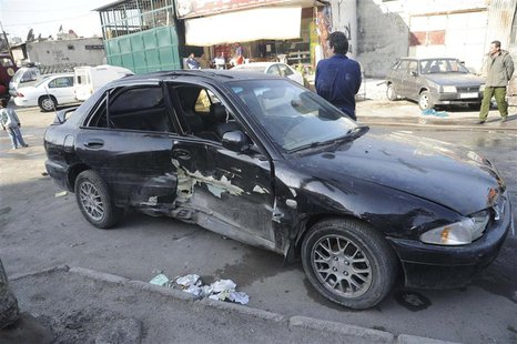 A damaged car is pictured after a mortar shell hit a textile factory at al-Dweil'a neighbourhood in Damascus on Sunday November 3, 2013, cau