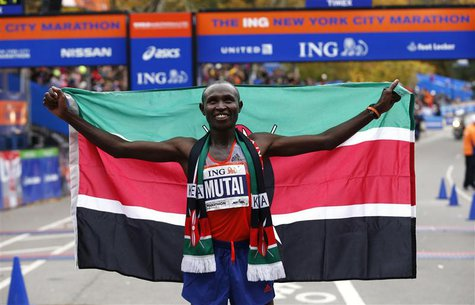 Geoffrey Mutai of Kenya holds up the Kenyan flag after winning the men's division of the New York City Marathon in New York, November 3, 201
