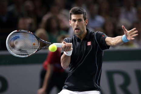 Novak Djokovic of Serbia hits a return to David Ferrer of Spain in their final match at the Paris Masters men's singles tennis tournament at