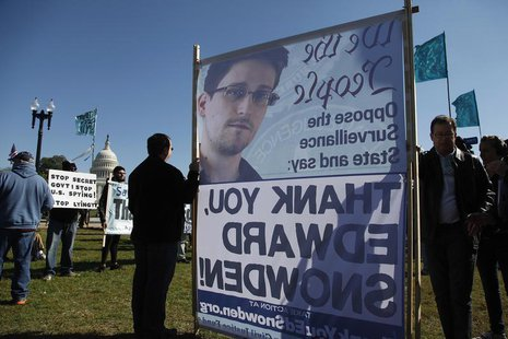 "Demonstrators hold signs supporting fugitive former NSA contractor Edward Snowden as they gather for the ""Stop Watching Us: A Rally Against"
