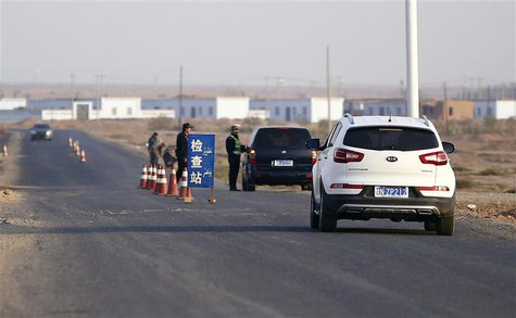 A police officer stops a car to check for identifications at a checkpoint near Lukqun town, in Xinjiang province in this October 30, 2013 fi