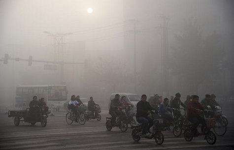 Residents ride bicycles along a street amid heavy haze in Xingtai, Hebei province November 3, 2013. REUTERS/China Daily