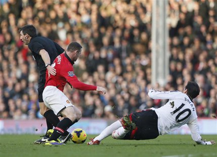 Manchester United's Wayne Rooney (C) collides with referee Lee Probert (L) as he is challenged by Fulham's Bryan Ruiz during their English P