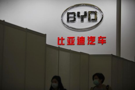 Women walk in front of the logo of Chinese car manufacturer BYD (Build Your Dreams) Auto stage before the opening of the 15th Shanghai Inter