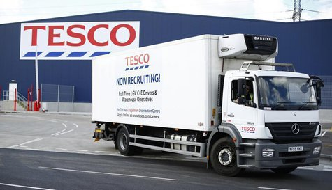 A lorry with job advertisements on its side leaves a Tesco distribution centre in Dagenham, east London August 12, 2013. REUTERS/Andrew Winn