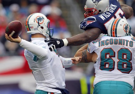 Miami Dolphins guard Richie Incognito (68) tries to stop New England Patriots defensive tackle Vince Wilfork (top R) from sacking Dolphins q