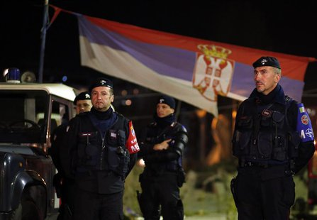 Italian Carabinieri, who are members of the NATO Kosovo Force (KFOR), stand in front of a Serbian national flag as they secure the main brid