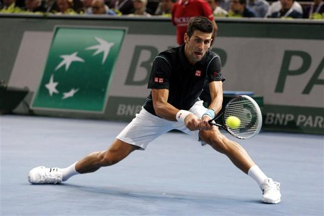 Novak Djokovic of Serbia hits a return to David Ferrer of Spain in the men's singles final match at the Paris Masters men's singles tennis t