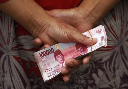 A woman holds Indonesian rupiah banknotes in front of a Bank Indonesia mobile bank in Jakarta July 15, 2013. REUTERS/Beawiharta