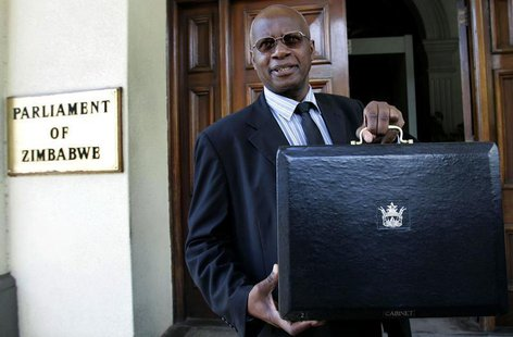 Zimbabwe's Patrick Chinamasa holds up a briefcase containing the government's budget at the Parliament buildings in Harare, January 29, 2009