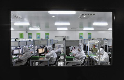 Employees work at a production line inside a factory exporting cameras used in mobile phones to Africa, in Shenyang, Liaoning province, Octo