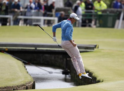 Sweden's Henrik Stenson jumps over the Swilcan Burn after chipping onto the first green during the final round of the British Open golf cham