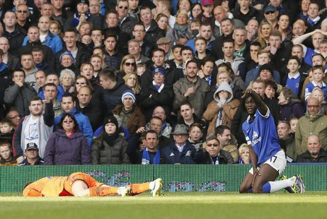 Tottenham Hotspur's goalkeeper Hugo Lloris (L) lies injured after a collision with Everton's Romalu Lukaku (R) during their English Premier