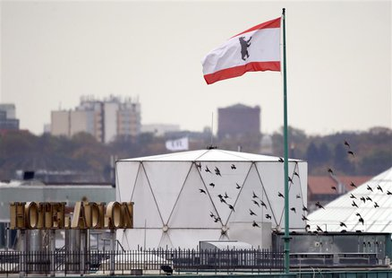 Birds fly beside a white covered structure and a Berlin city flag next to the roof of the British embassy in Berlin, November 5, 2013. REUTE