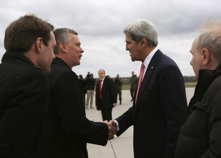 U.S. Secretary of State John Kerry (2nd R) is greeted by Poland's Defence Minister Tomasz Siemoniak (2nd L) upon his arrival at Lask Air For