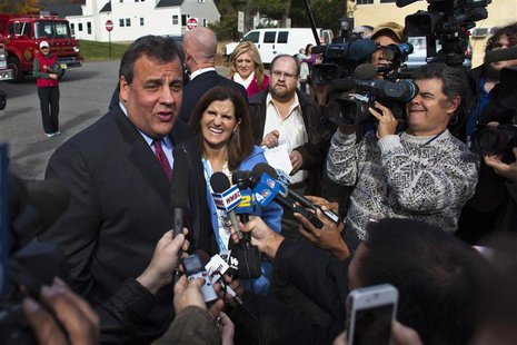 New Jersey Governor Chris Christie (L) speaks to the media, as his wife Mary Pat smiles, after casting his vote during the New Jersey govern