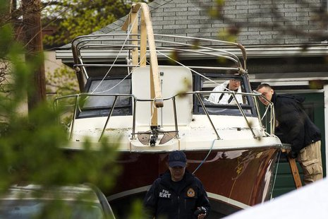 Members of the FBI Evidence Recovery Team inspect the boat where Boston Marathon bombing suspect Dzhokhar Tsarnaev was hiding at 67 Franklin