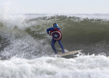 A participant dressed as Captain America surfs during the third annual Rockaway Halloween surf competition at Rockaway Beach in the Queens b