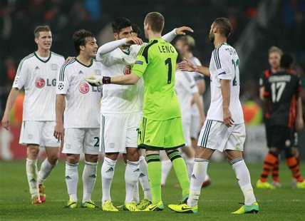 Bayer Leverkusen's players greet each other after their Champions League soccer match against Shakhtar Donetsk at the Donbass Arena stadium