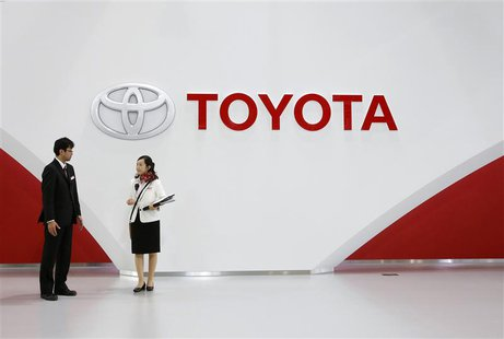 Staff stand under Toyota Motor's logo at the company's showroom in Tokyo November 6, 2013. Toyota Motor Corp will raise its operating profit