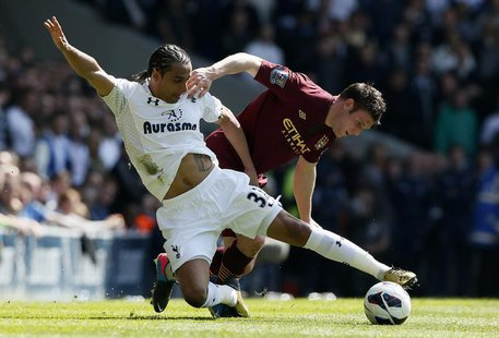Tottenham Hotspur's Benoit Assou-Ekotto (L) challenges Manchester City's James Milner during their English Premier League soccer match at Wh
