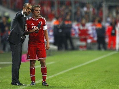 Bayern Munich's coach Pep Guardiola (L) talks to Philipp Lahm during their German first division Bundesliga soccer match against Borussia Mo
