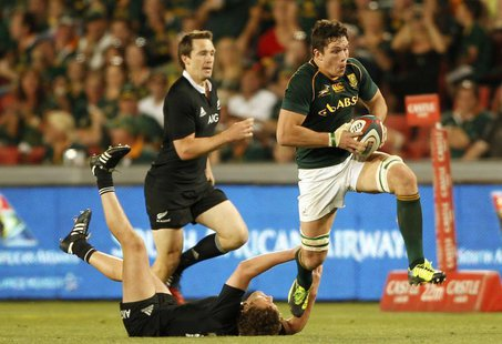 New Zealand's All Blacks Tawera Kerr-Barlow (L) tackles South Africa's Francois Louw, during the final round of the Rugby Championship at El
