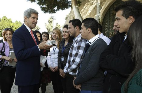U.S. Secretary of State John Kerry greets Palestinian youth who presented him with a gift box at Manger Square in Bethlehem November 6, 2013