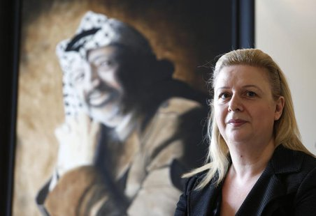 Suha Arafat poses near a portrait of her late husband and Palestinian leader Yasser Arafat before watching the wreath laying ceremony after