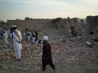 Tribesmen gather at a damaged house after a missile struck in Dandi Darpakheil village on the outskirts of Miranshah, the main town in the N