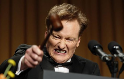 Comedian Conan O'Brien smashes a gavel as he speaks during the White House Correspondents Association Dinner in Washington April 27, 2013. R