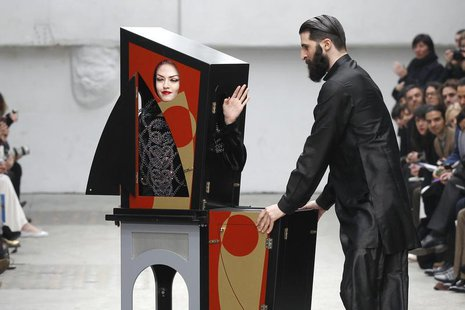 A magician performs with a model who presents a creation by Indian designer Manish Arora as part of his Fall-Winter 2011/2012 women's ready-