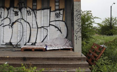 A homeless person sleeps under a blanket on the porch of a shuttered public school covered with graffiti in a once vibrant southwest neighbo