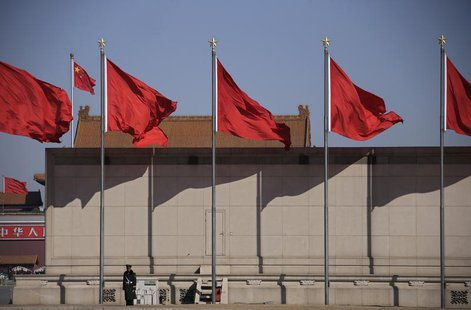 A paramilitary policeman stands guard under flags outside the Great Hall of the People during the third plenary session of the National Peop