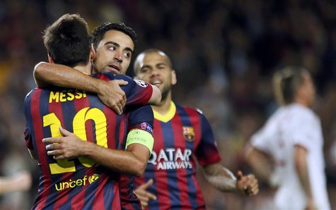 Barcelona's Lionel Messi (L) is congratulated by team mates Xavi (C) and Dani Alves after scoring his second goal against AC Milan during th