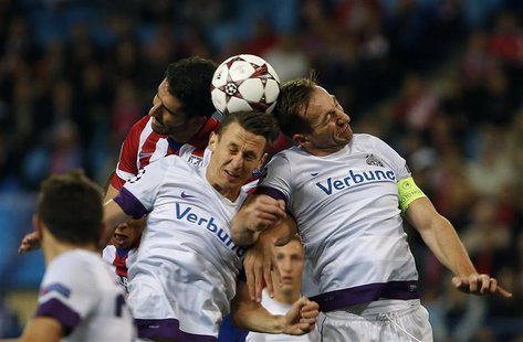 Atletico Madrid's Raul Garcia (L) fights to head the ball with Austria Vienna's Florian Mader (C) and Manuel Ortlechner during their Champio