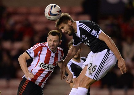 Sunderland's Phil Bardsley (L) challenges Southampton's Jos Hooiveld during their English League Cup fourth round soccer match at the Stadiu