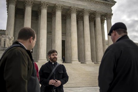 Christian clergy members gather outside the U.S. Supreme Court as it hears arguments in the case of Town of Greece, NY v. Galloway, in Washi